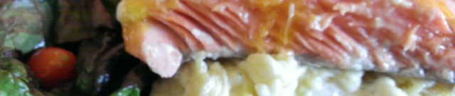 Medium rare coho salmon over potatoes with green salad. Photo by Ria Loader